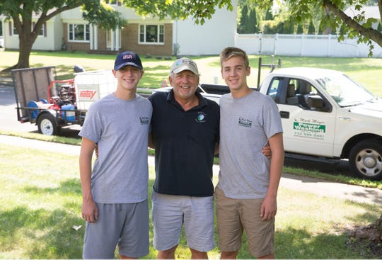 Mark Mayer, owner of Mark Mayer Power Washing demonstrates his work. Mayer, center with his grandson who now work with him, Evan Lowther, left, and Luke Lowther, right.