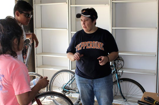 Jen Rogers talks with Nikki Jimenez and her son, Marco Gomez, at the Community Bike Shop. Marco was in need of a new bike to ride to high school this year.
