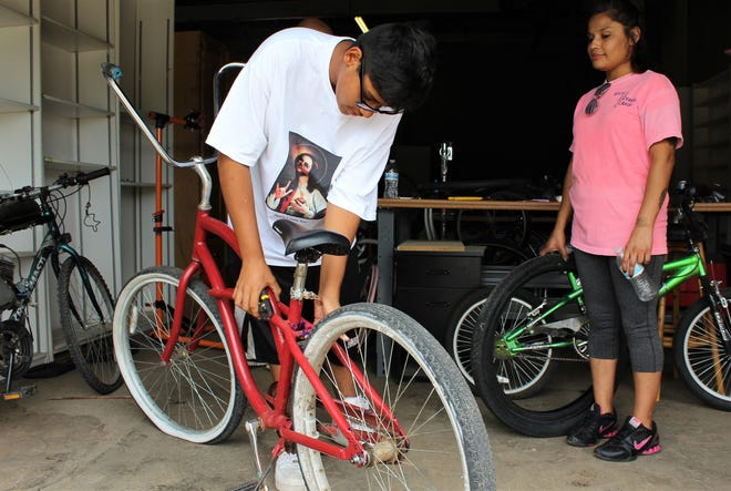 ATEMS student Marco Gomez checks out a bike at the Community Bike Shop on Walnut Street, while his mother, Nikki Jimenez watches.
