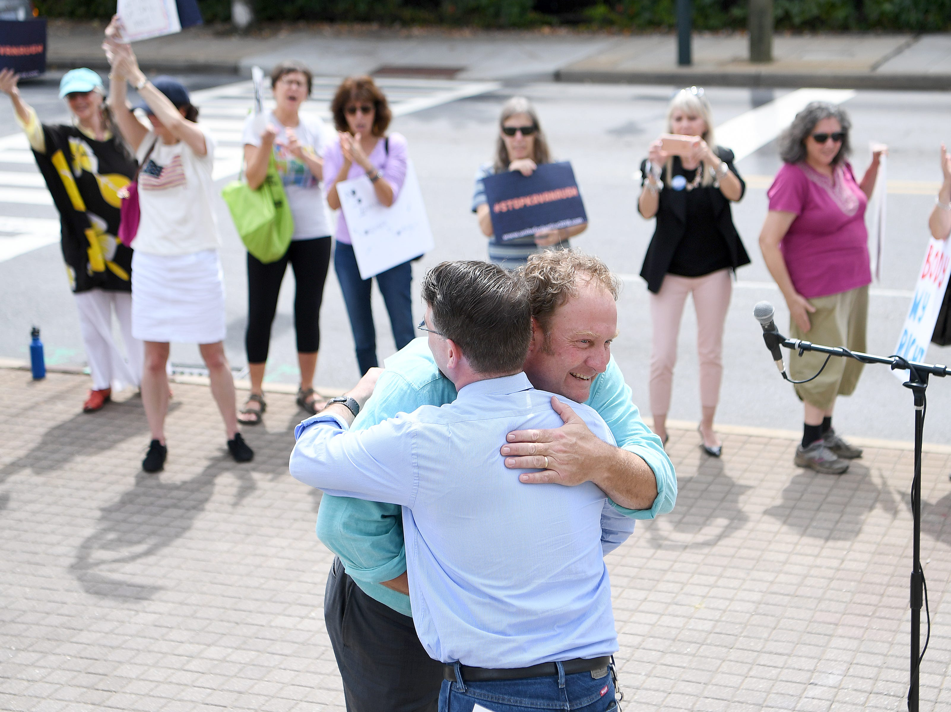 Congressional candidate Phillip Price, hugs Catori Swann, president of the Progressive Democrats of Buncombe County, before addressing the crowd during a protest against the hearing of Supreme Court nominee Judge Brett Kavanaugh in front of the federal building downtown on Wednesday, Sept. 5, 2018.