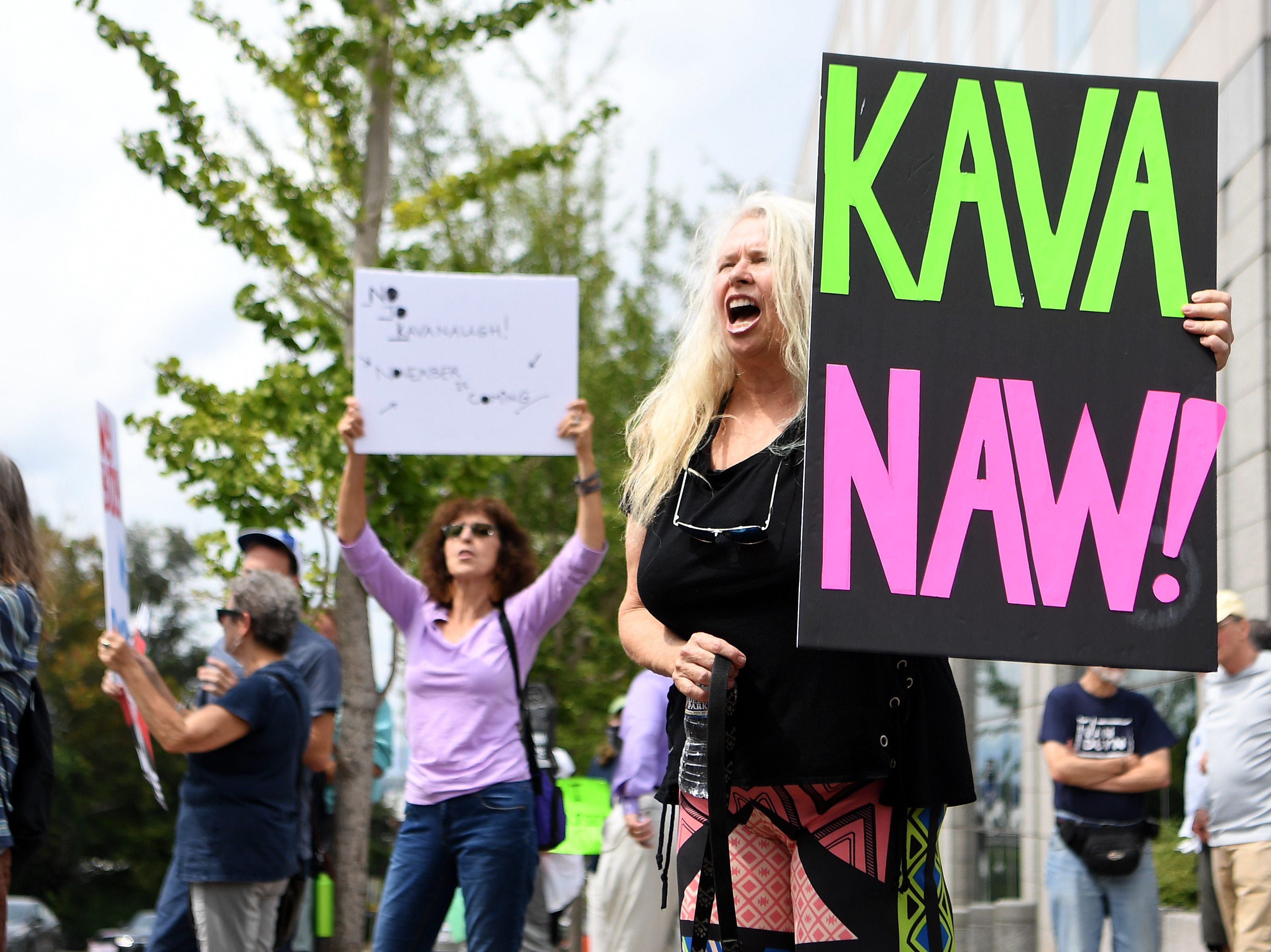 M.J. Taylor holds a homemade sign and chants at passing traffic during a protest against the hearing of Supreme Court nominee Judge Brett Kavanaugh in front of the federal building downtown on Wednesday, Sept. 5, 2018.