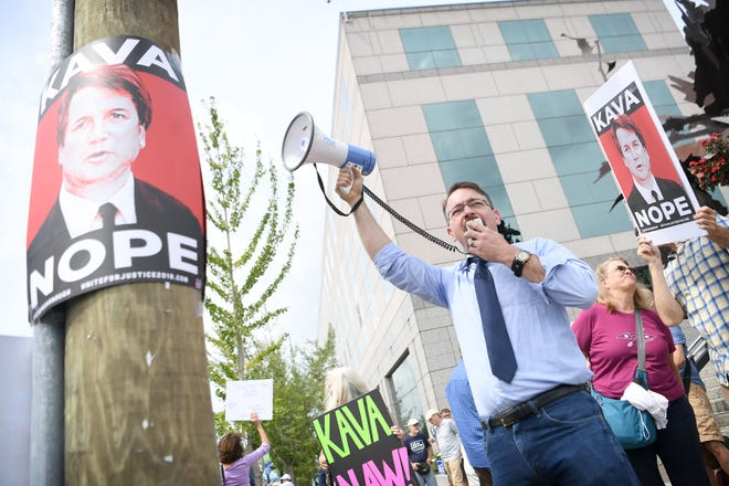 Catori Swann, president of the Progressive Democrats of Buncombe County, leads protestors in a chant with a megaphone during a protest against the hearing of Supreme Court nominee Judge Brett Kavanaugh in front of the federal building downtown on Wednesday, Sept. 5, 2018.