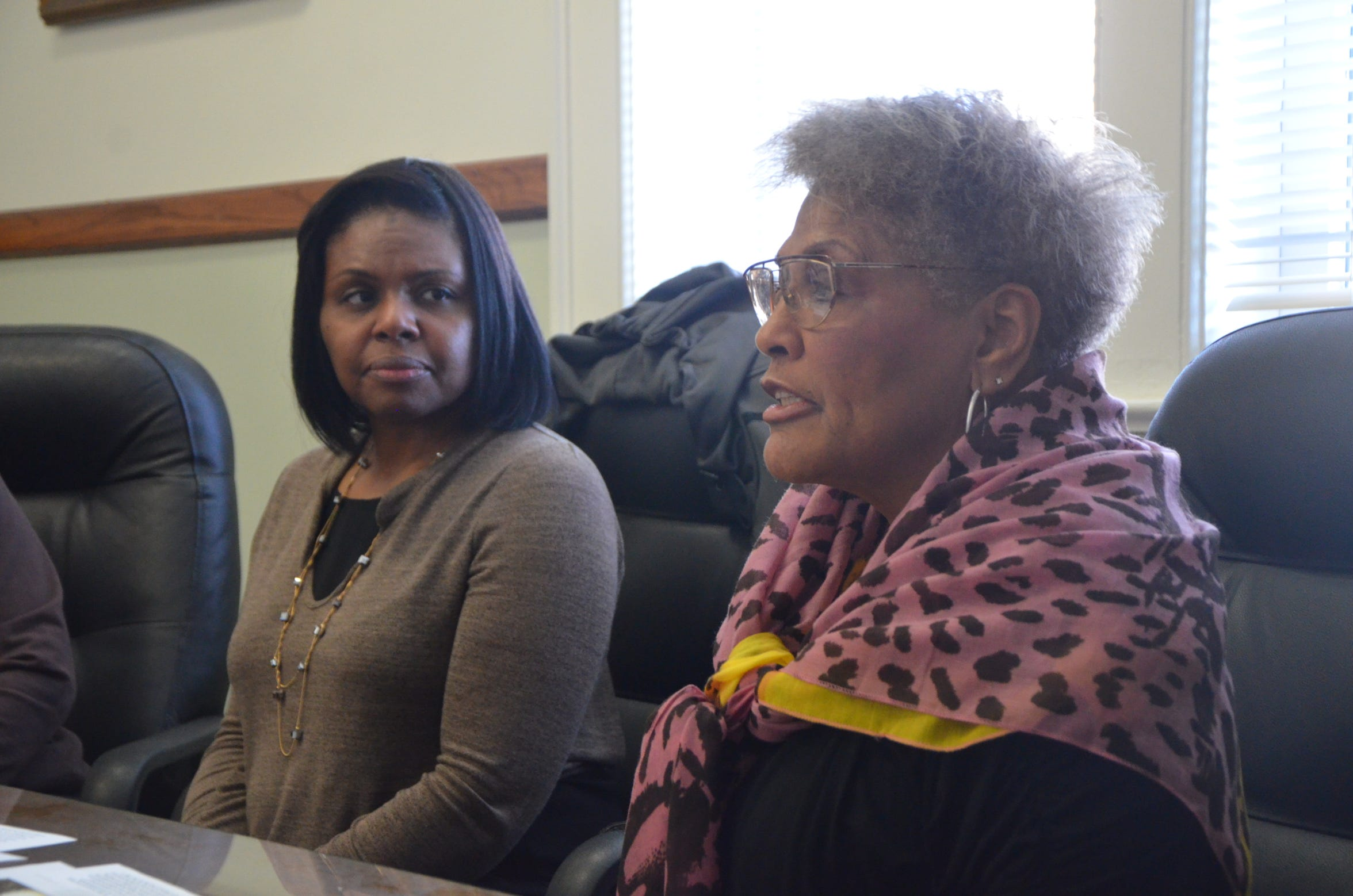 Kimberly Holley (left) listens as Betty Moorehead talks about her experiences growing up in Battle Creek's Bottoms neighborhood.