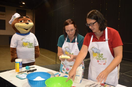 (L-R) Sugar Bear mascot, Liane Ford and Sarah Thompson of Post Consumer Brands bake their third-place winning cake at the Salvation Army of Battle Creek and Battle Creek Community Foundation's first Great BC Bake-Off.
