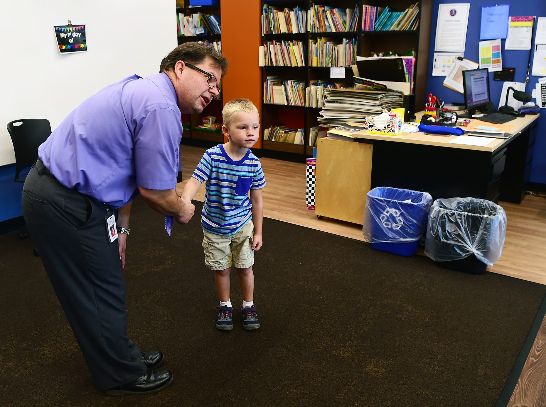 Mr. Joseph Shambo, a kindergarten teacher, talks with kindergarten student Greyson Rieg during the first day of classes at Owego Elementary School, Owego, Wednesday, September 5, 2018.