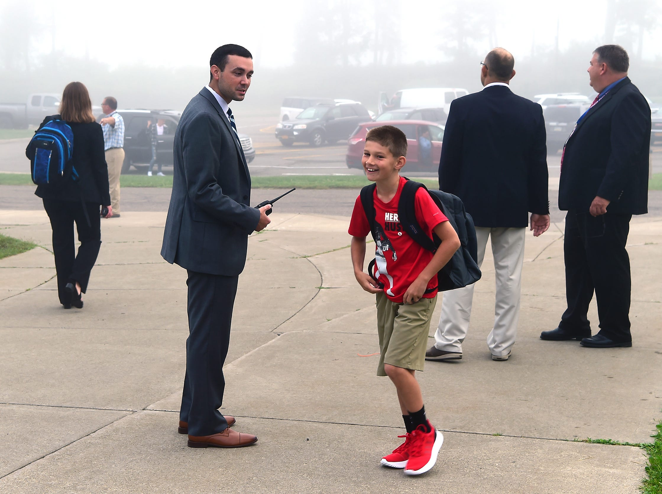 Owego Free Academy Assistant Principal Phil Schofield greets middle school student Jack Buchsbaum during the morning drop-off at the first day of classes at Owego Apalachin Middle School and Owego Free Academy, Wednesday, September 5, 2018.