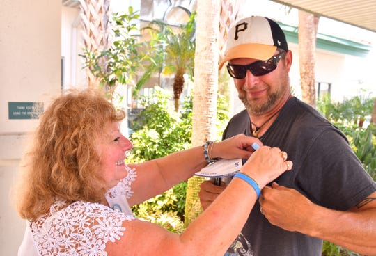In a September 2018 photo, Martha Duffy pins a blue ribbon on Eric Kerner of Cocoa Beach. Duffy was set up outside the Cocoa Beach Library on what would have been her husband David Duffy's 72nd birthday, passing out blue ribbons and information on prostate cancer for Prostate Cancer Awareness Month.