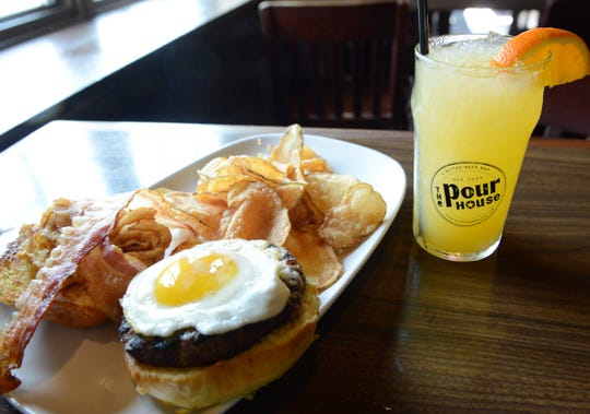 A Hangover Burger comes with a fried egg, bacon, chipotle aioli,smoked cheddar and crispy onion straws. It's served here with a Weekend Krush, made with Three Olives Orange vodka, orange juiceand orange Pedialyte.