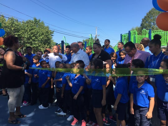 Camden Mayor Frank Moran (white shirt, left), Camden County Freeholder Jeff Nash (white shirt, right), city councilwoman Marilyn Torres and councilman Angel Fuentes (pink shirt) prepare to cut the ribbon at Alberta Woods Park with children from Mastery McGraw Elementary School.