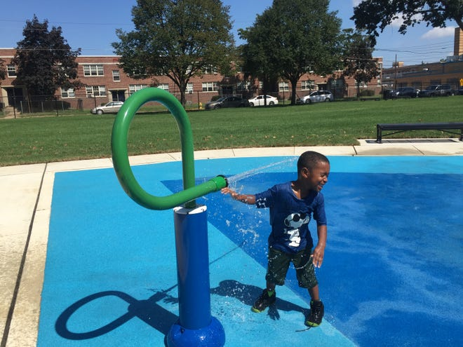 Brennan Richardson, age 4, gets doused by a water spout at the splash pad at Alberta Woods Park in East Camden.