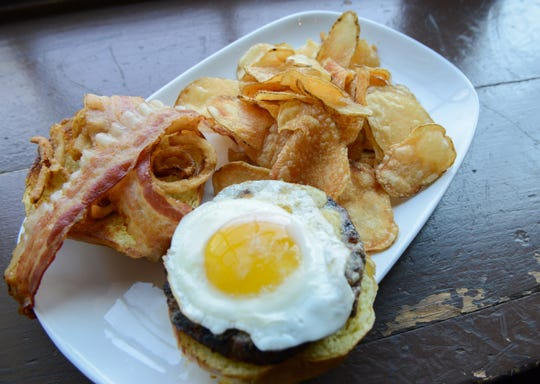 A Hangover Burger with a fried egg, bacon, chipotle aioli,smoked cheddar and crispy onion straws is served with a side of chips at the Pour House.