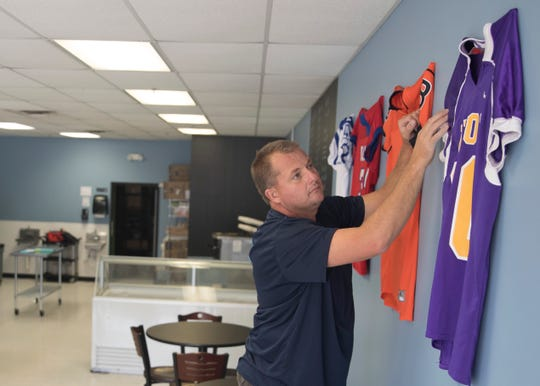 Chillicothe 2° ice cream shop owner Mike Kelly straightens the football jerseys he has gotten to hang in the ice cream shop Wednesday afternoon. To honor the local teams, he hopes to get more jerseys from local schools.