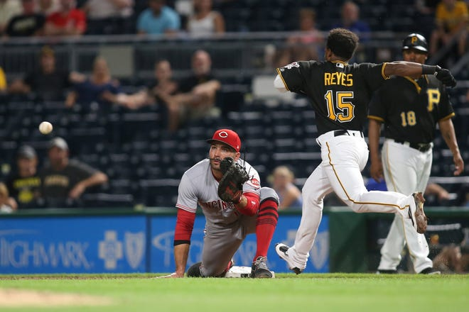 Pittsburgh Pirates third baseman Pablo Reyes (15) beats a throw to Cincinnati Reds first baseman Joey Votto (19) for a single to record his first major league hit during the fourth inning at PNC Park.