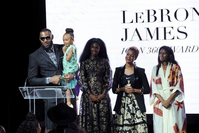 LeBron James holds his daughter Zhuri as he accepts the Harlem Fashion Row's ICON 360 Award for his contribution to fashion and philanthropy at the HFR fashion show and awards ceremony before the start of New York Fashion Week, Tuesday, Sept. 4, 2018.