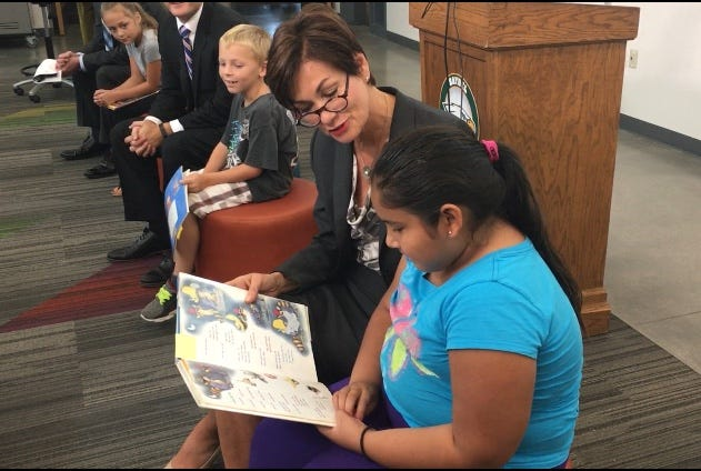 Gov. Kim Reynolds jointly reads a book with Guadalupe Sanchez, 8, a third grader at Cornell Elementary School, on Sept. 5, 2018 in Saylor Township, which is just north of Des Moines, Iowa.