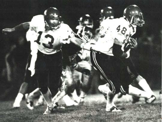 Centerville quarterback David DenHartog hands the ball to running back Shawn Oden during a 1984 football game.