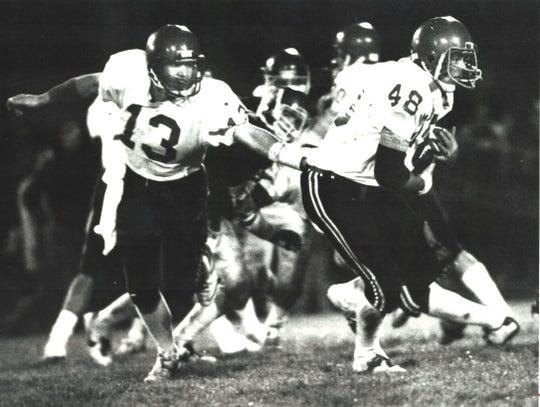 Centerville quarterback David DenHartog hands the ball to running back Shawn Oden during a 1984 football game.