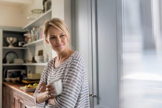Thoughtful Woman Holding Coffee Mug By Window