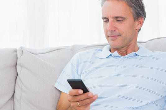 Man Relaxing On His Couch Sending A Text