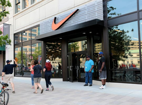 People look at the outside of the Nike store on Woodward Ave. as they pass by in Detroit in May 2016.