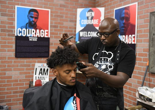 Volunteer barber Rodney Tyson of Lavish Styles N Cuts gives community coordinator Joseph Middlebrooks, 23, a haircut during a Cuts and Coding educational event for young black males at the Ford Research and Engagement Center in Detroit.