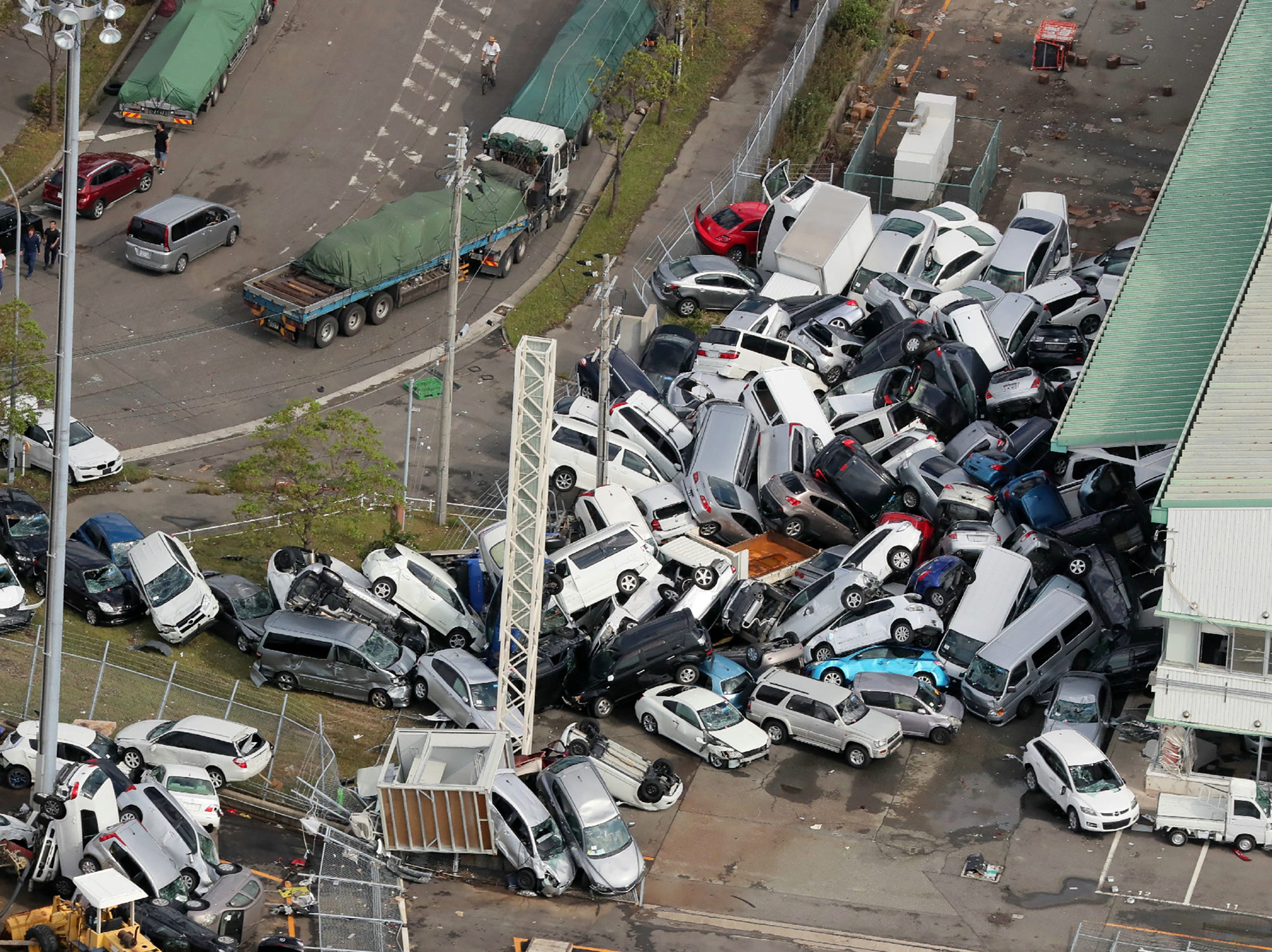 An aerial view from a Jiji Press helicopter shows vehicles piled in a heap due to strong winds in Kobe, Hyogo prefecture on Sept. 5, 2018, after typhoon Jebi hit the west coast of Japan. The toll in the most powerful typhoon to hit Japan in a quarter century to nine, with thousands stranded at a major airport because of storm damage.