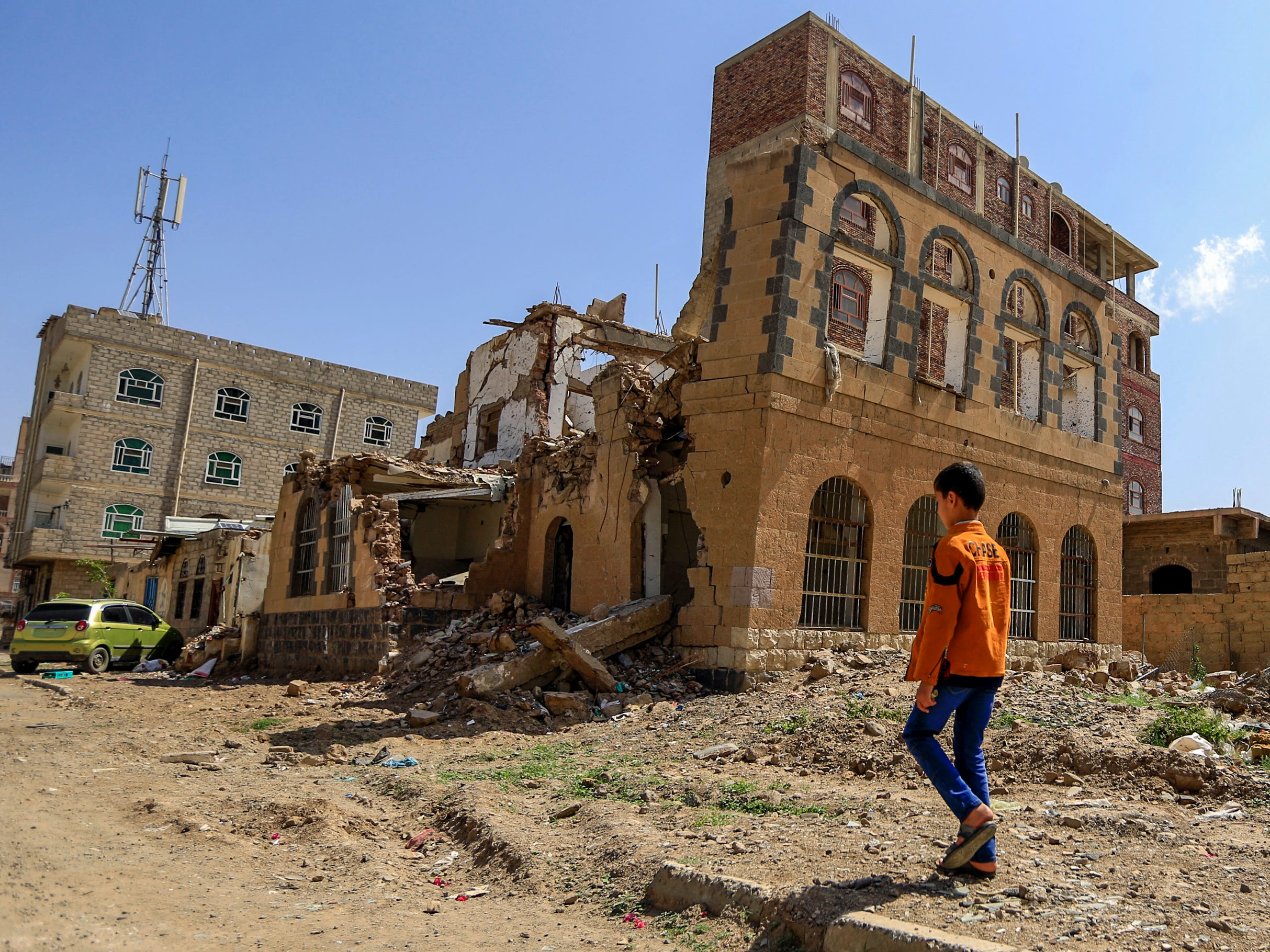 A Yemeni child walks toward a building that was reportedly destroyed in Saudi-led coalition air strike in the capital Sanaa on Sept. 5, 2018.