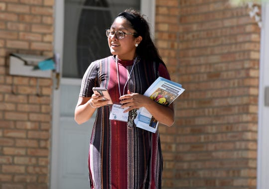 Field organizer Viviana Alamillo canvasses in Lansing and collects voter data on issues on behalf of For Our Future.