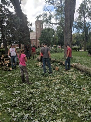Volunteers move tree limbs following tornadoes touching down in Lomira and Brownsville.