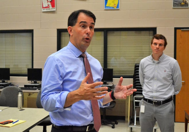 On a visit to Oconto Falls High School on Tuesday, Sept. 4, 2018, Gov. Scott Walker on Tuesday discusses TEACH grants being awarded to consortia of schools around the state to provide technology training for educators. At right is Corey Jeffers, director of technology for the Oconto Falls School District.