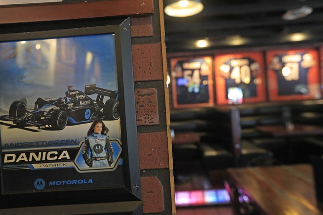 Danica Patrick memorabilia is displayed at the Poison Ivy Pub in her hometown of Roscoe Illinois, with signed Chicago Bears jerseys in the background.