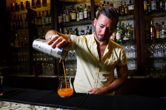 """Regan Cannon pours a """"mocktail"""" at Husk Greenville bar on Tuesday, Sept. 4, 2018."""