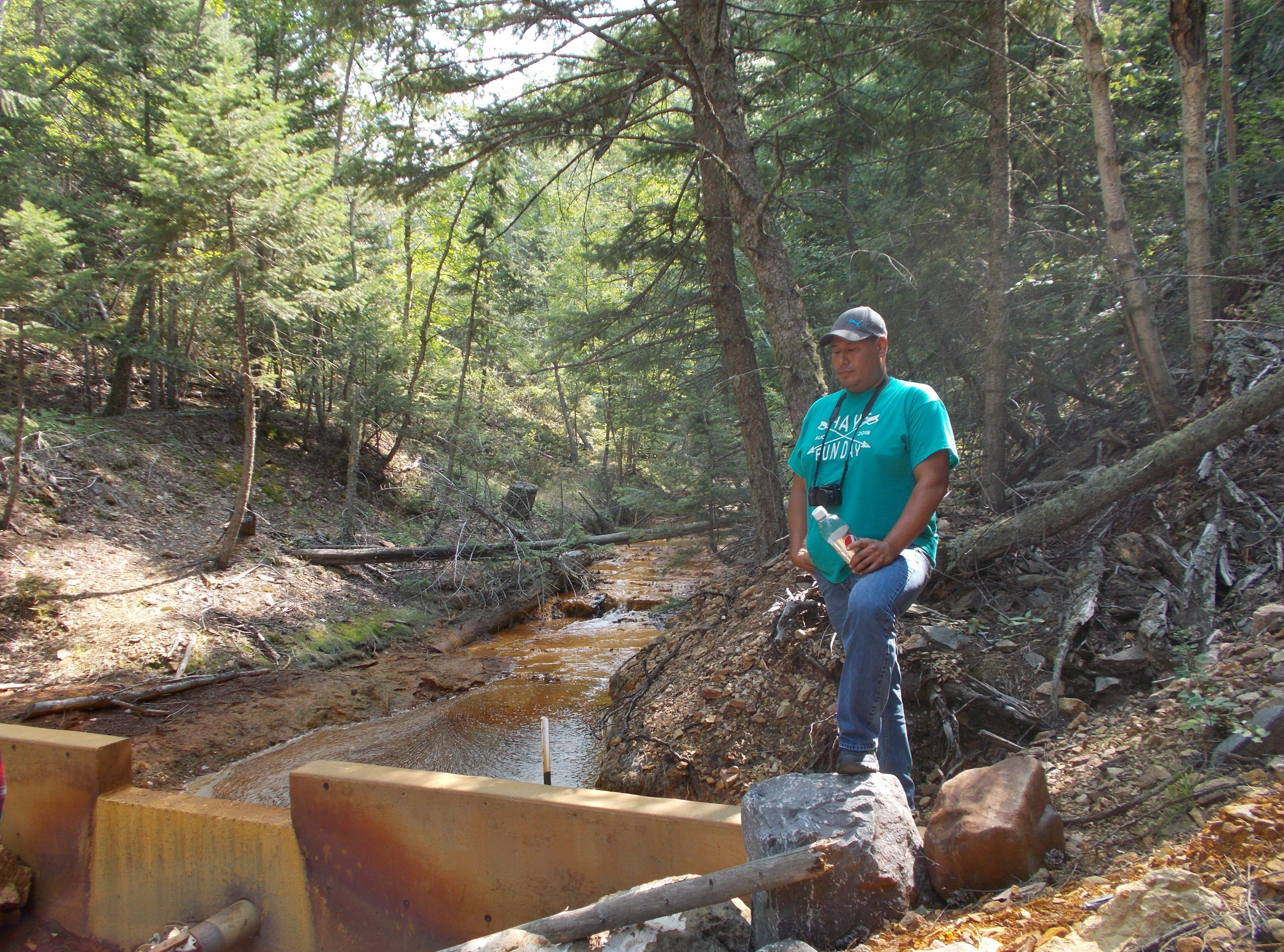 Mitchell Healy, coordinator of the Fort Belknap Indian Community's Water Quality Program, stands near a creek polluted with acid rock drainage. Reservation water quality officials say pollution has made its way into reservation streams.