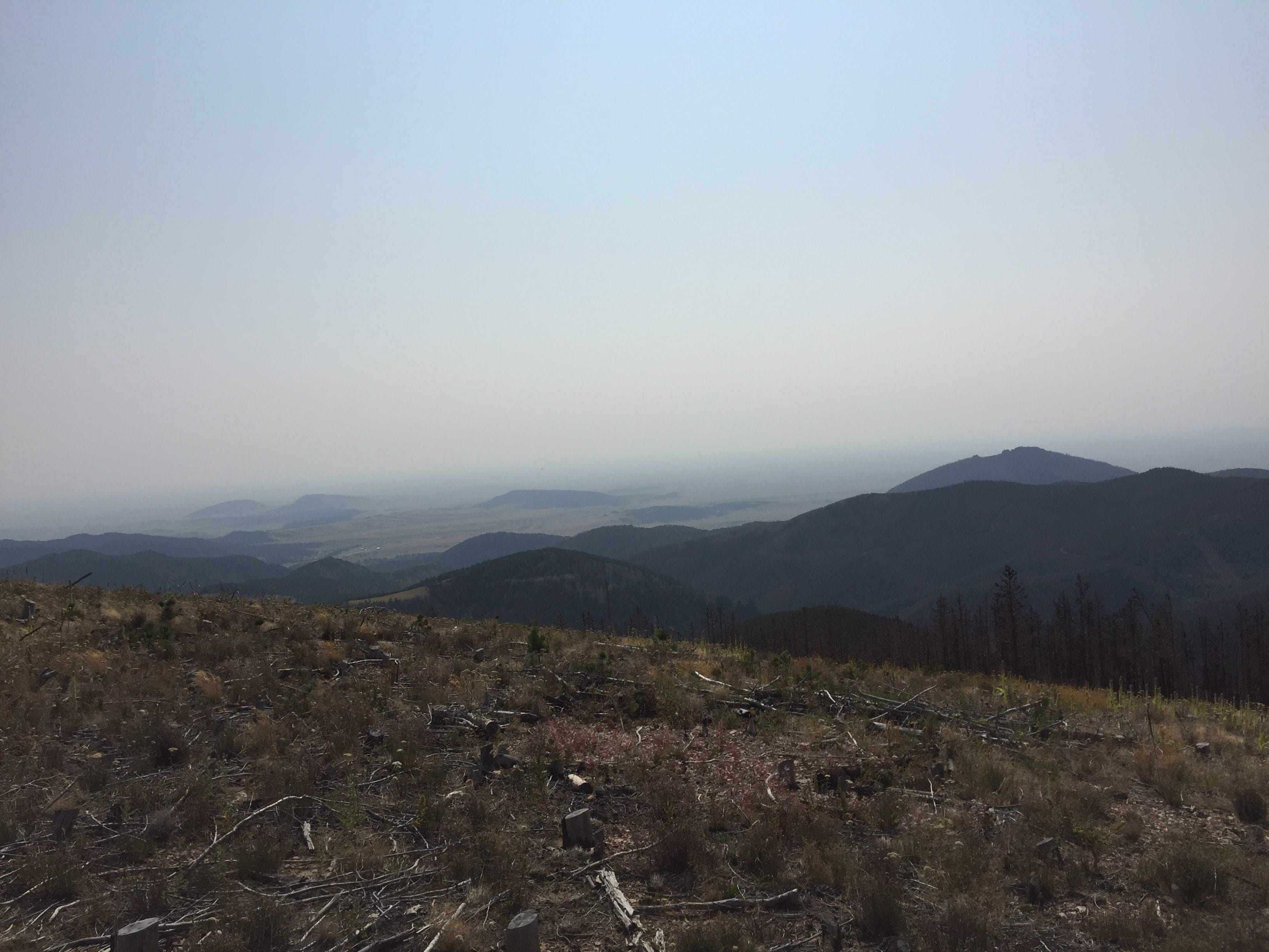 In August, smoke from wildfires blanketed northcentral Montana's Little Rocky Mountains, an outlier mountain range where gold mining has caused extensive water quality problems.