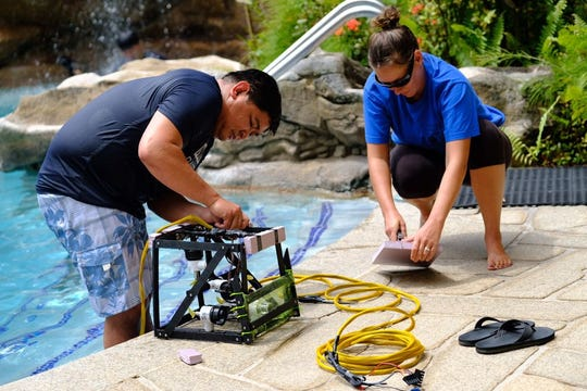 (From Left) Jude Mesa and Deirdra O'Donnell, science teachers at Southern High School, test the buoyancy of their marine robot.