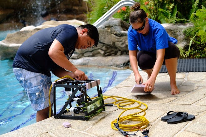 Jude Mesa, left,, and Deirdra O'Donnell, science teachers at Southern High School, test the buoyancy of their marine robot.