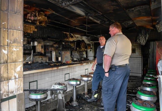 Madisonville Fire Chief Ray Wyatt, center, and Assistant Chief Jeff Baldwin inspect the interior of Ferrell's Hamburgers on North Main Street in Madisonville Wednesday. The historic eatery suffered a fire overnight Tuesday, but the owner plans to rebuild, September 5, 2018.