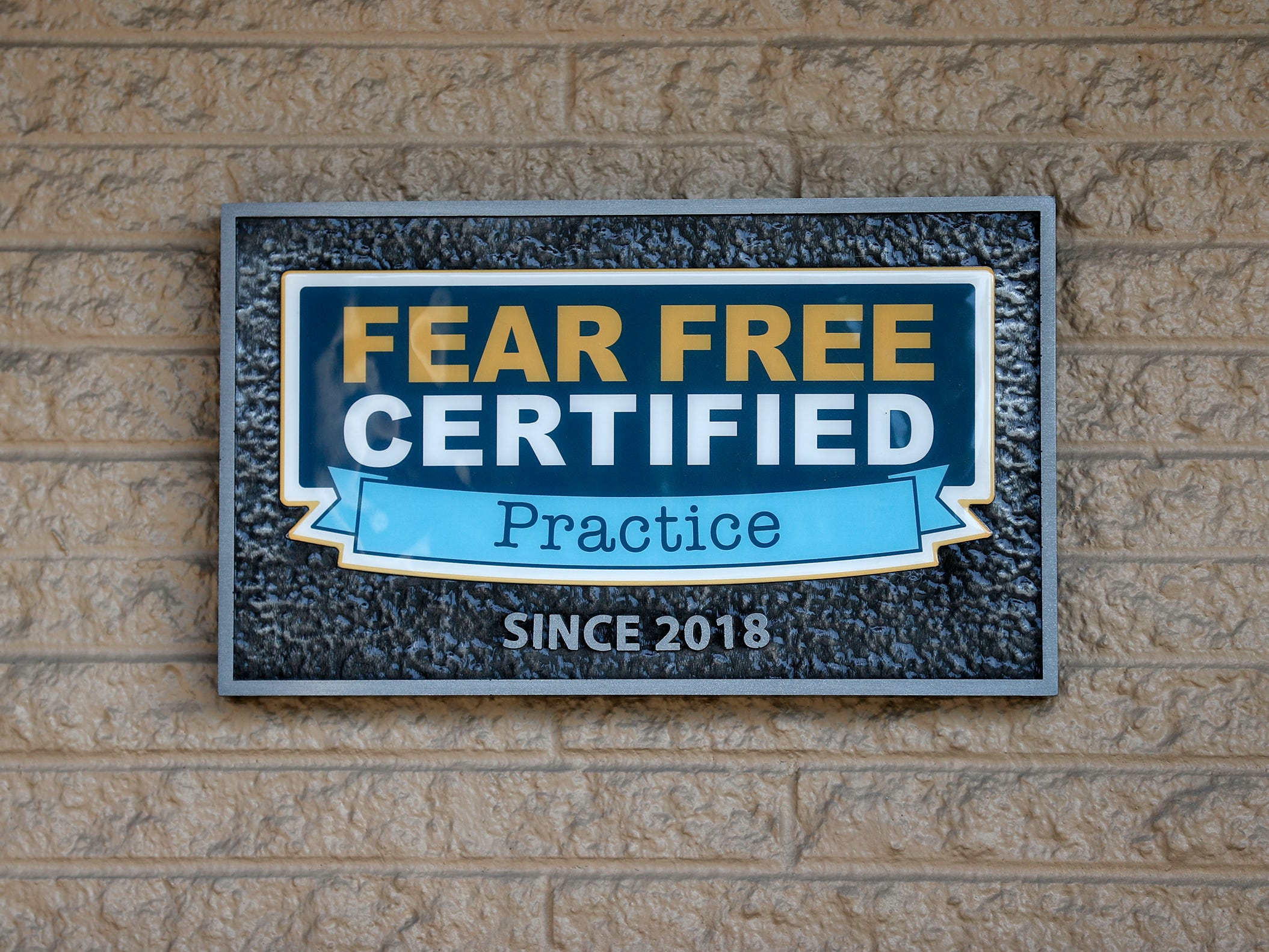 A sign on the front of Paw Patch Place Animal Hospital shows a recent certification, Friday, Aug. 31, 2018.  The veterinary clinic is the only one in Indiana to earn special fear free certification from an international program that aims to help vets reduce anxiety for pets prone to feel stressed in their offices.