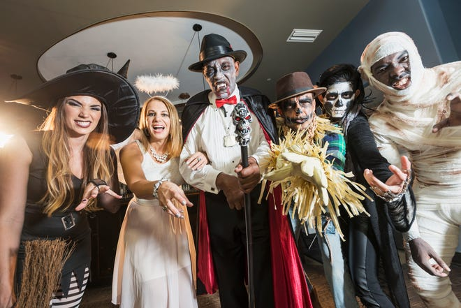 A group of six multi-ethnic men and women of mixed ages at a halloween party wearing costumes.
