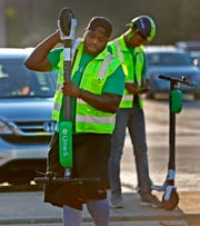 George Kelly, left, and Andre Licatovich retrieve Lime scooters to ready them for redeployment, in Broad Ripple, Wednesday, Sept. 5, 2018.