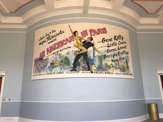 "An original 1950s ""An American In Paris"" movie billboard advertisement is on display in the Robert Adam room at the Palladium in Carmel."