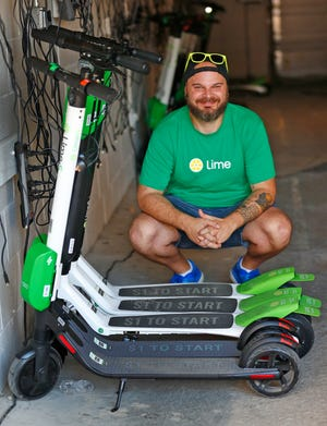 Nathan Hasse, Indianapolis Operations Manager for Lime, poses by charging Lime scooters, Wednesday, Sept. 5, 2018.