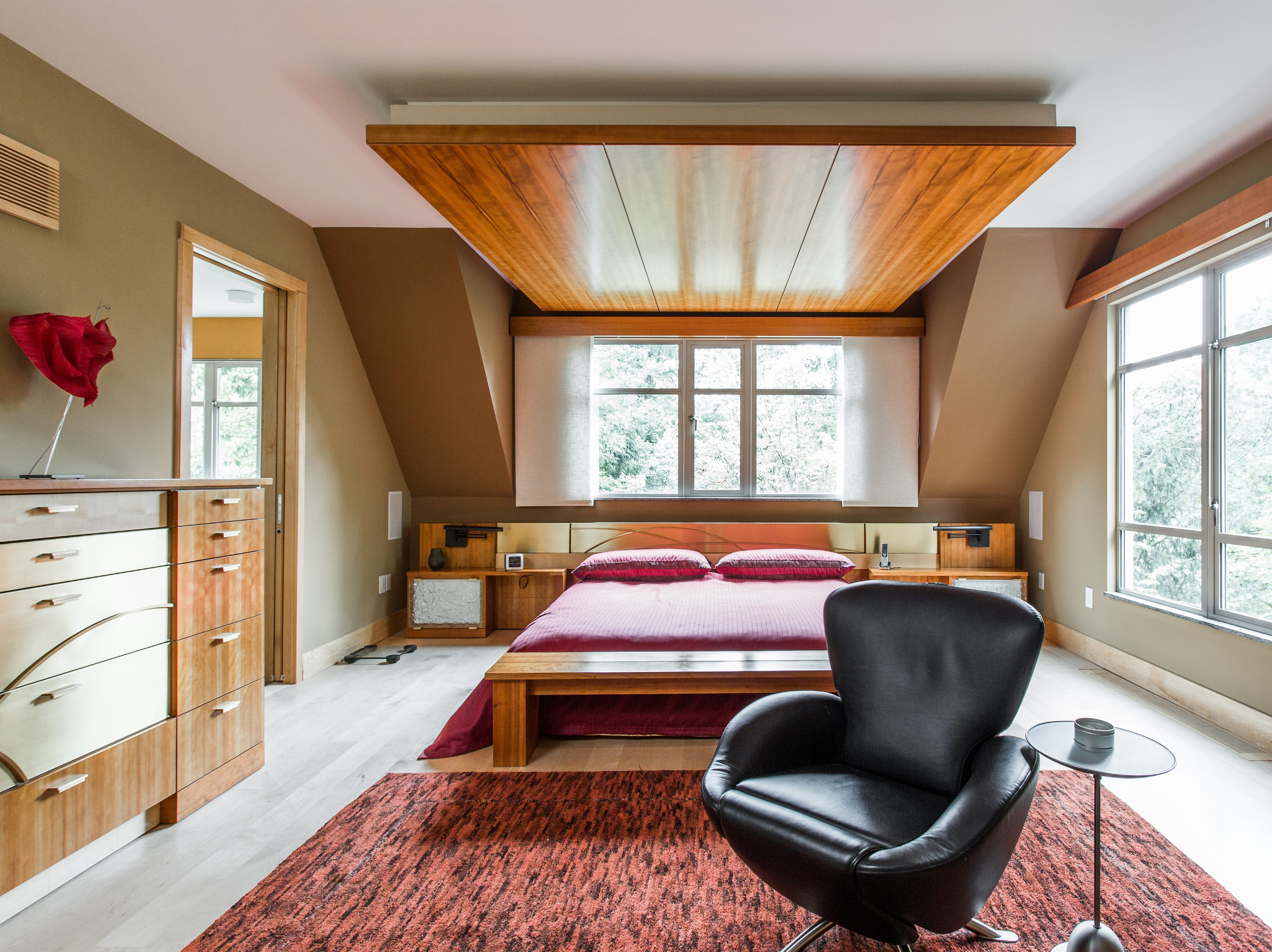 The master bedroom features views of the wooded lot.