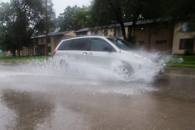 Vehicles drive through flash flooding on Wednesday, Sept. 5, 2018, along lower Riverside Drive in Iowa City.