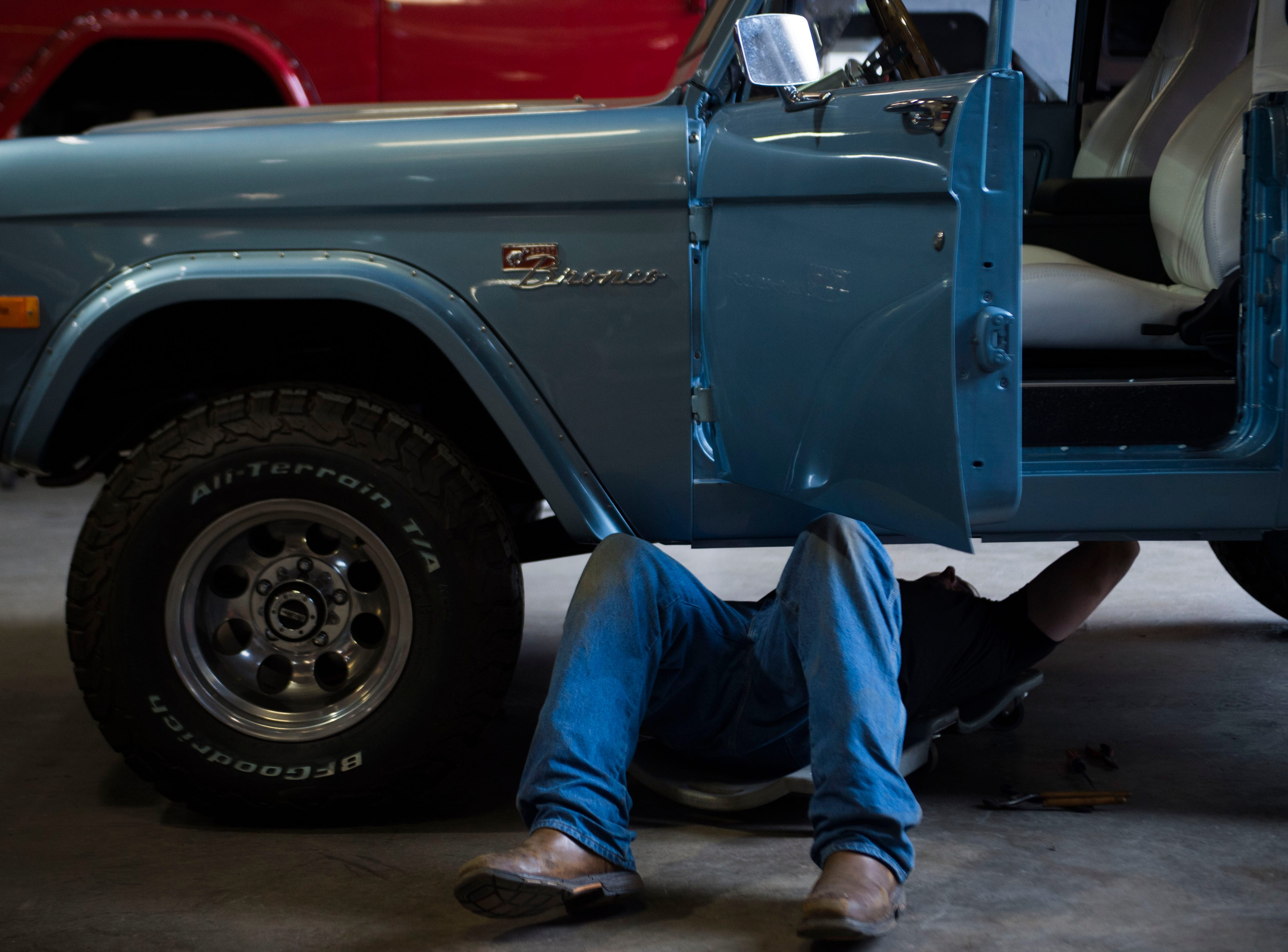 RJ Vickers works under a Bronco at Krawlers Edge, which specializes in Ford Bronco restoration, in Seymour on Friday, Aug. 31, 2018.