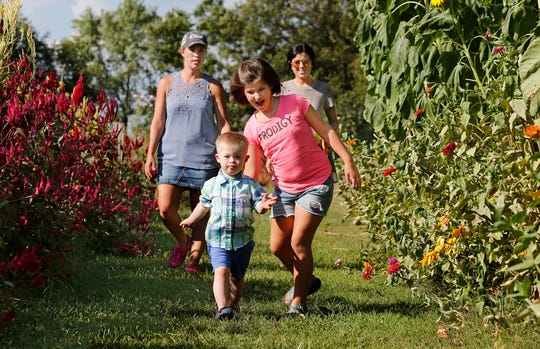 Foxx Goetz, 4, and his sister Reeslin, 9, run ahead of their mother Stefani Goetz and Rebekah Whisler (Foxx's nanny) at 21 Petals flower farm Tuesday off County Road 700 S south of Lafayette. Customers can choose from numerous flower varieties at the U-pick farm.