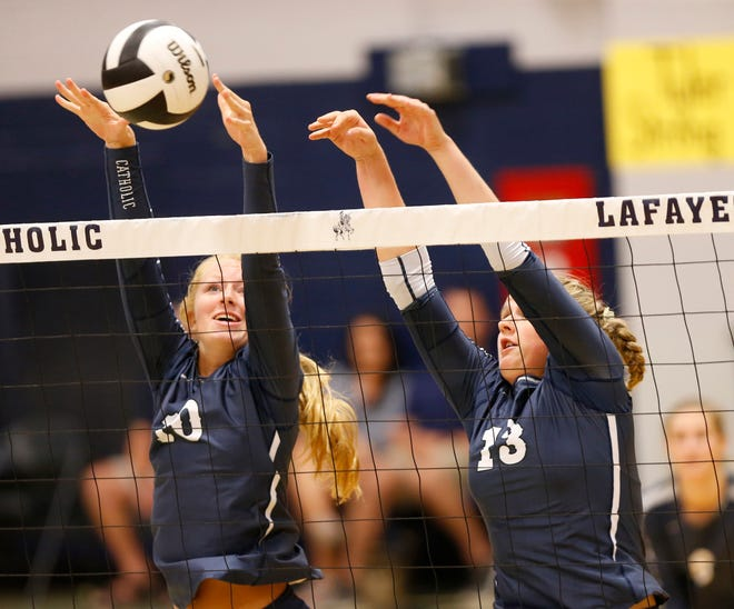 Maddie McPherson, left, and Jozee Evans of Central Catholic combine for the block against Lafayette Jeff as the two teams meet to Spike Out Cancer Tuesday, September 4, 2018, in Lafayette. CC defeated Jeff 25-14, 25-17, 25-13.