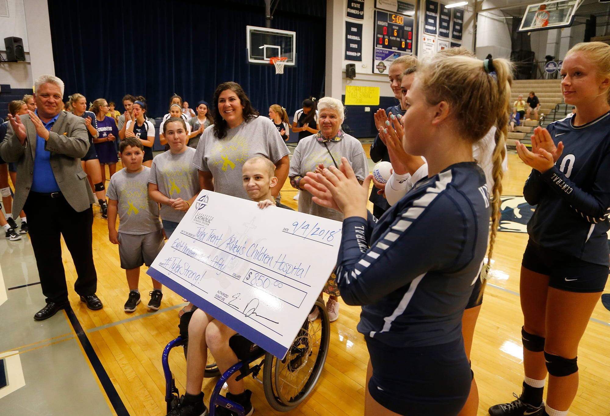 Central Catholic players present Tyler Trent with a check to benefit Riley Children's Hospital before meeting Lafayette Jeff to Spike Out Cancer Tuesday, September 4, 2018, in Lafayette. Trent is a sophomore at Purdue battling cancer. CC defeated Jeff 25-14, 25-17, 25-13.