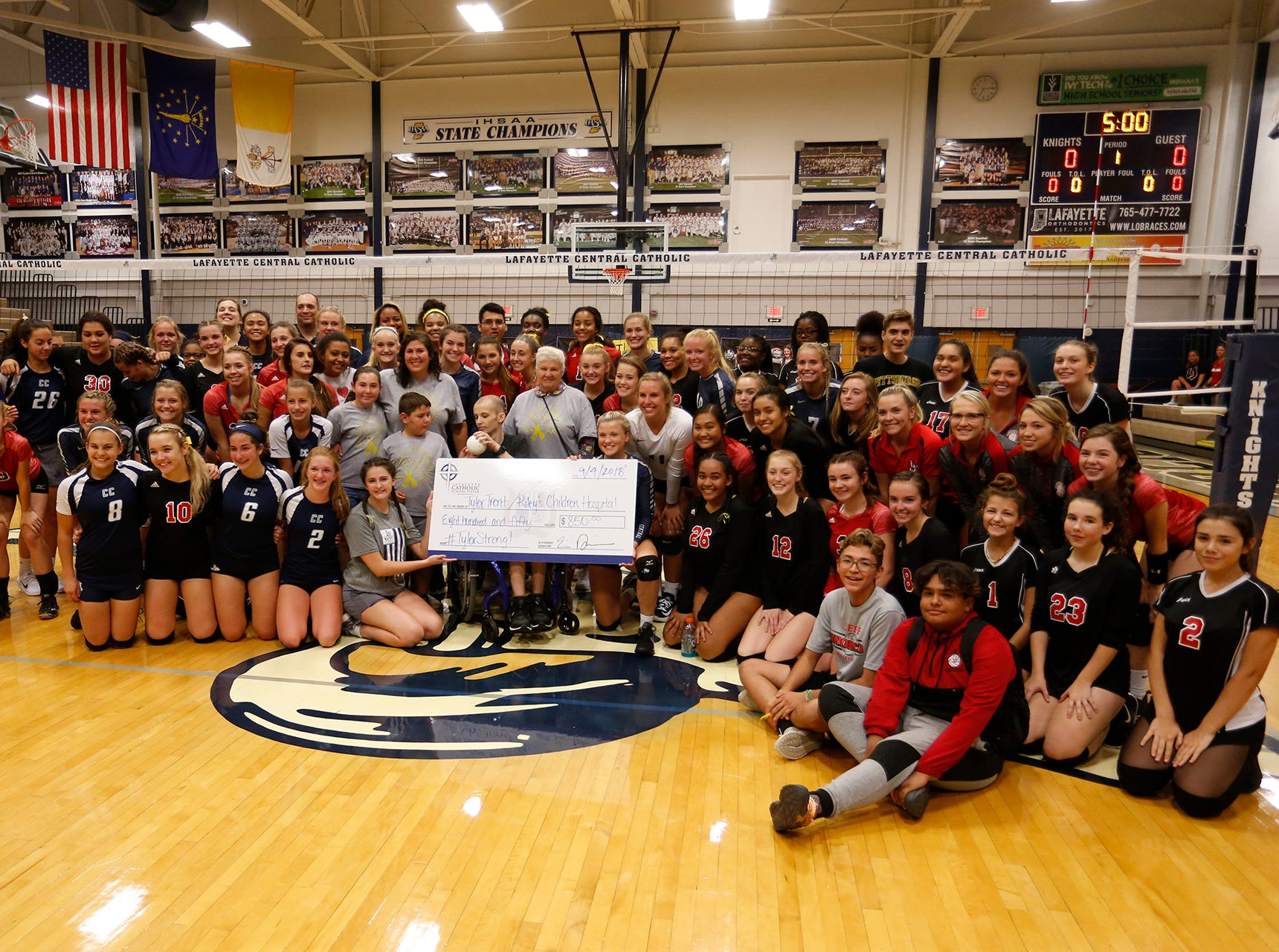 Players from Central Catholic and Lafayette Jeff pose a group photo with Tyler Trent before playing to Spike Out Cancer Tuesday, September 4, 2018, in Lafayette. Trent is a sophomore at Purdue battling cancer. CC defeated Jeff 25-14, 25-17, 25-13.