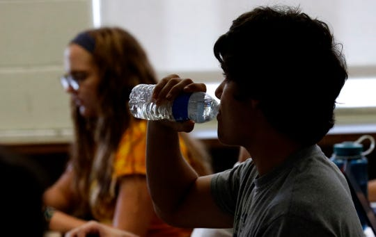 A student takes a drink of water during a statistics class Wednesday, Sept. 5, 2018, at Lancaster High School. The school was built with no air conditioning, and on hot days temperatures can be in the upper 80s in the hottest classrooms.